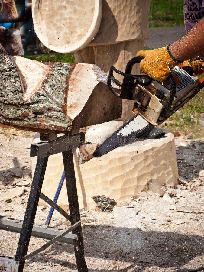 Sculpteur en bois à l'aide de la tronçonneuse image libre de droits