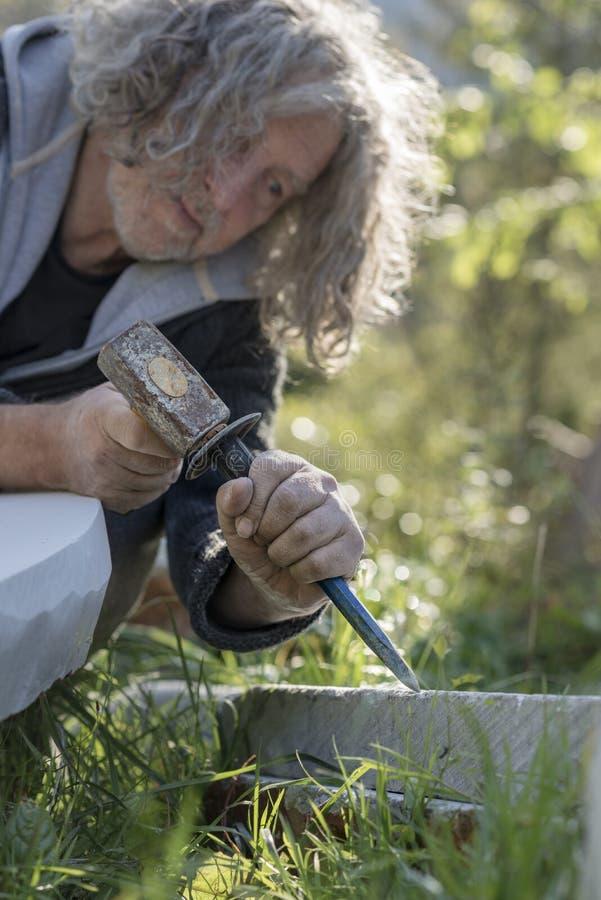 Sculpteur supérieur sculptant dans la pierre dehors photographie stock