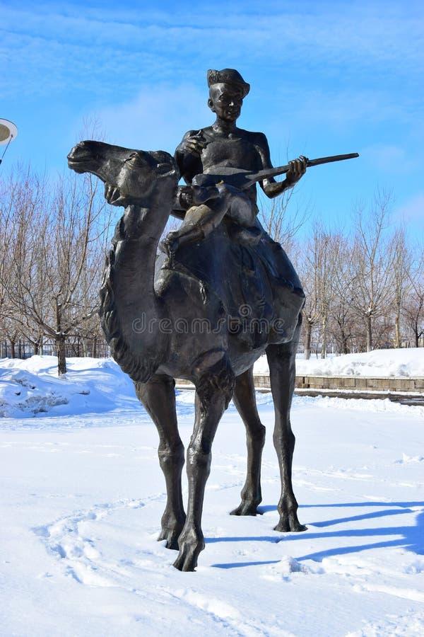 Sculptez comporter un homme avec un instrument de musique de ficelle sur un chameau image libre de droits