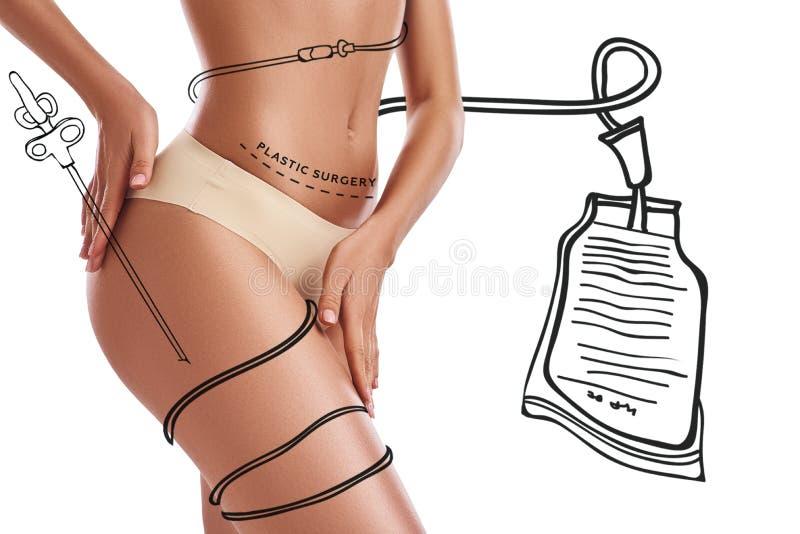 Sculptez votre corps La jeune femme dans les sous-vêtements montre sa belle cuisse tout en se tenant sur le fond blanc avec images libres de droits