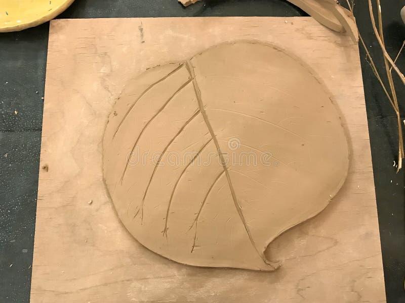 Sculpting Lehm im Prozess Vorbereitung eines Lehmflacheisens in Form eines Blattes Der Prozess des Zeichnens eines Bildes Beschne stockfoto