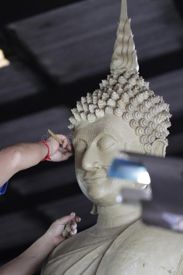 Sculptor artist creating a bust sculpture with clay, hand of craftman working on buddha statue, closeup face of buddha royalty free stock photography