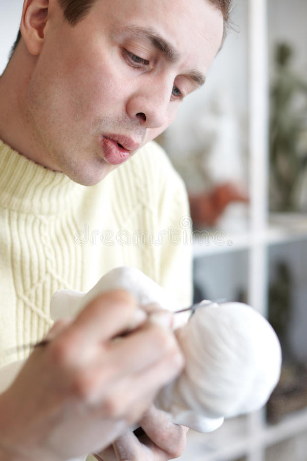 Sculptor carefully works on plaster statuette. With sculptor tools and blows off plaster crumbs royalty free stock photos