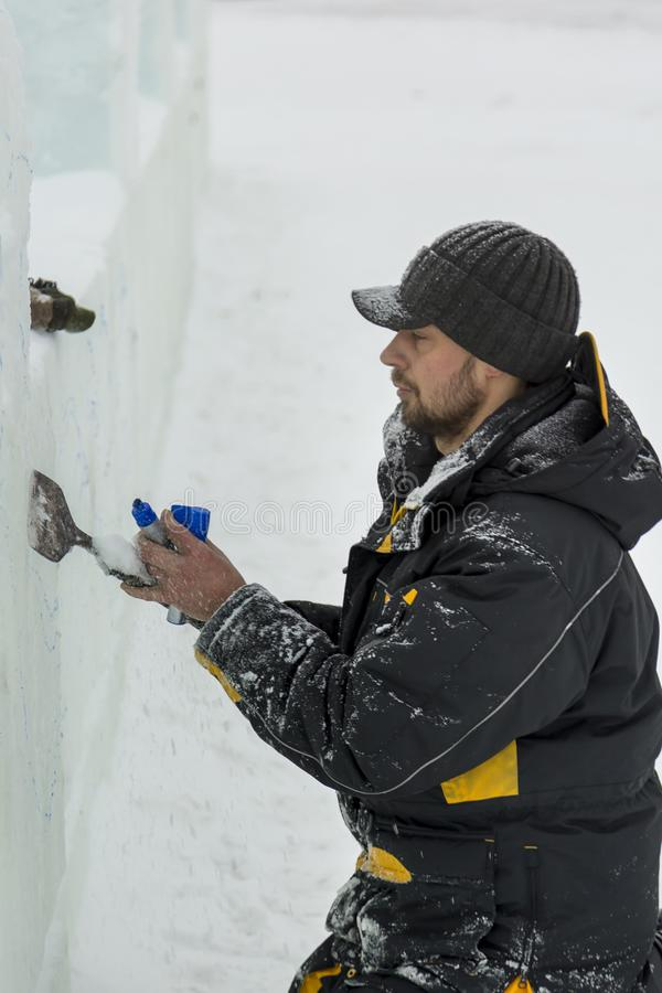 Portrait of a sculptor with a chisel in his hands. The sculptor cuts an ice figure out of an ice block with a chisel stock photos