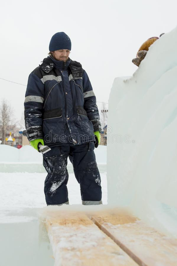 Portrait of a sculptor with a chisel in his hands. The sculptor cuts an ice figure out of an ice block with a chisel royalty free stock photos