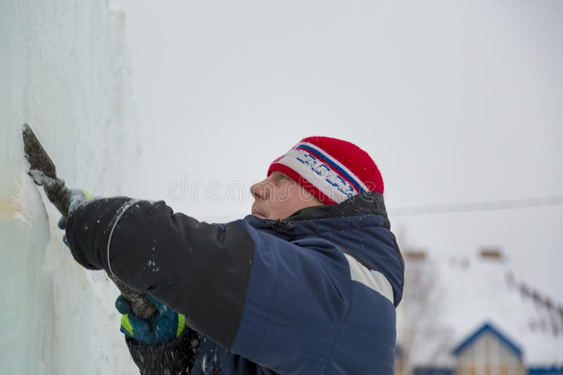 Portrait of a sculptor with a chisel in his hands. The sculptor cuts an ice figure out of an ice block with a chisel stock photography