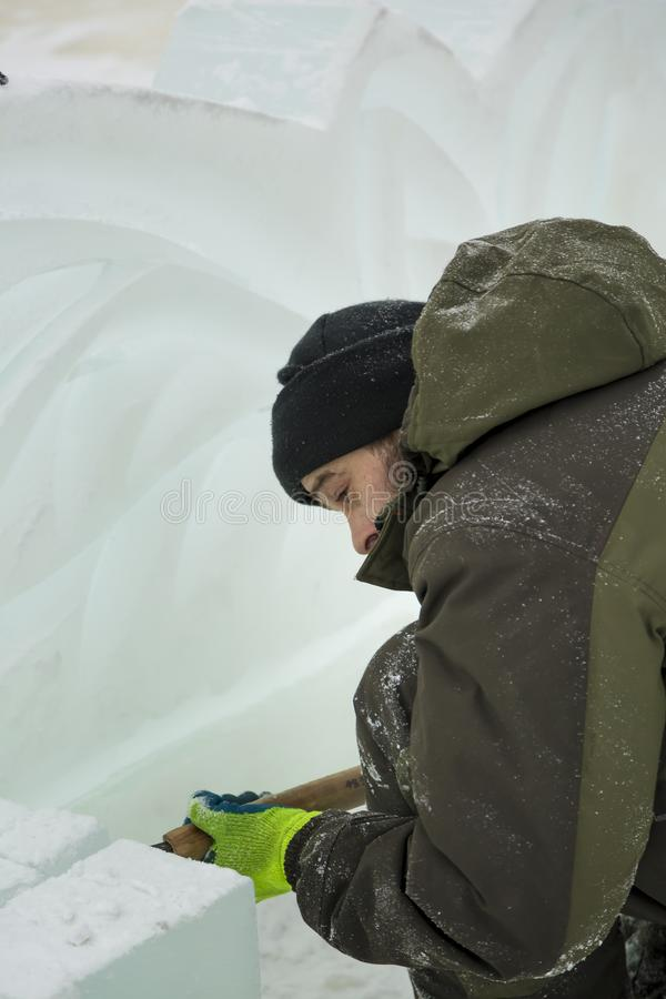 Portrait of a sculptor with a chisel in his hands. The sculptor cuts an ice figure out of an ice block with a chisel royalty free stock images