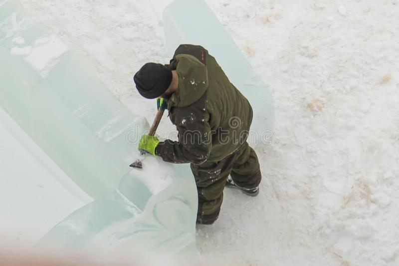 Portrait of a sculptor with a chisel in his hands. The sculptor cuts an ice figure out of an ice block with a chisel stock photo