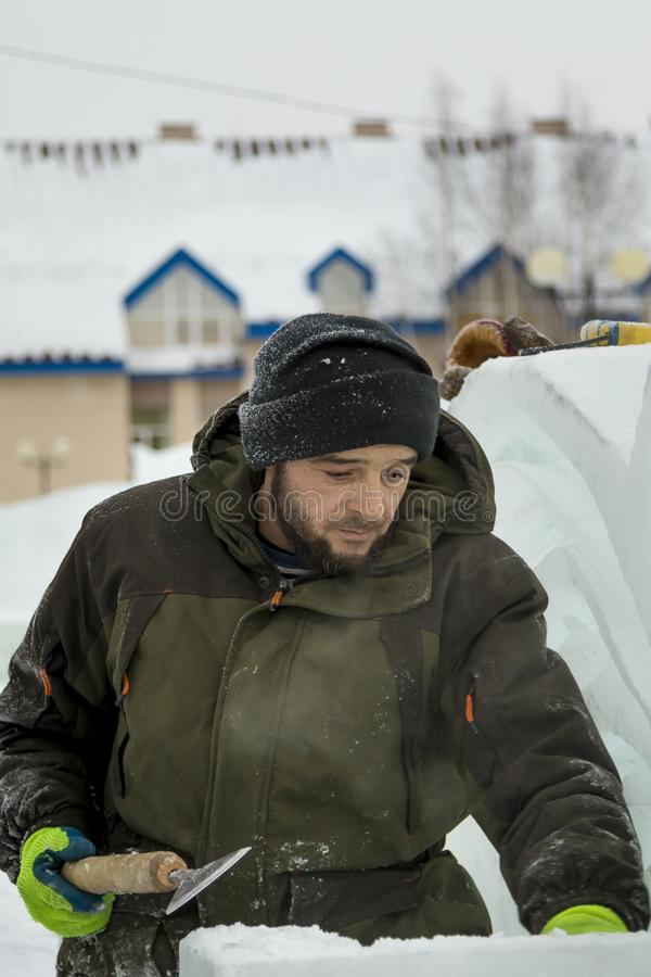 Portrait of a sculptor with a chisel in his hands. The sculptor cuts an ice figure out of an ice block with a chisel royalty free stock photography
