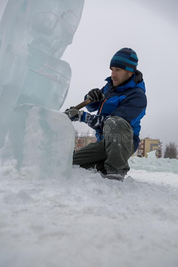 Portrait of a sculptor with a chisel in his hands. The sculptor cuts an ice figure out of an ice block with a chisel stock images