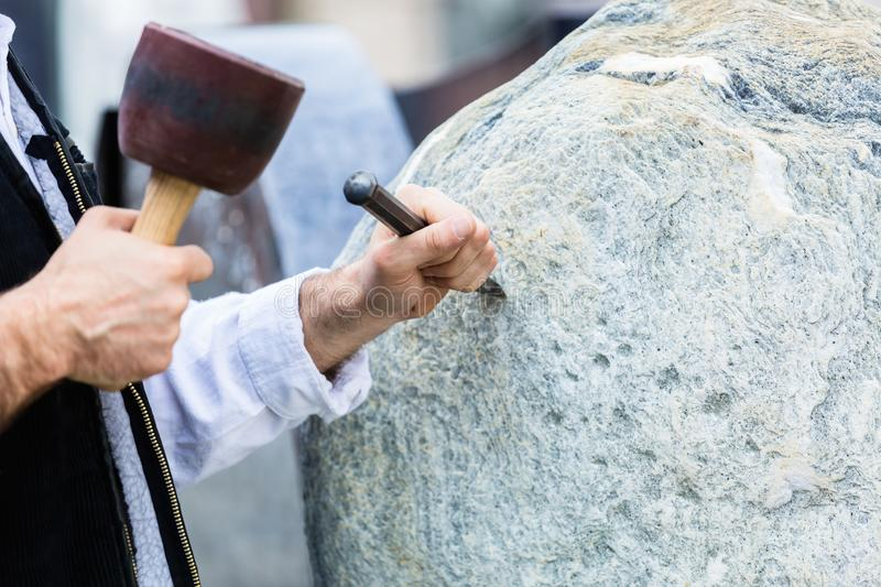 Sculptor with mallet and cutter working on erratic block stock images