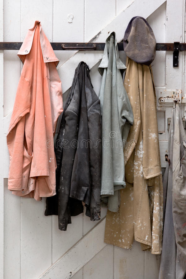 Sculptor's Coats. Four pastel coloured coats and a hat hanging on a white door. The coats are covered in white plaster, well worn and lived in. The coats royalty free stock photo