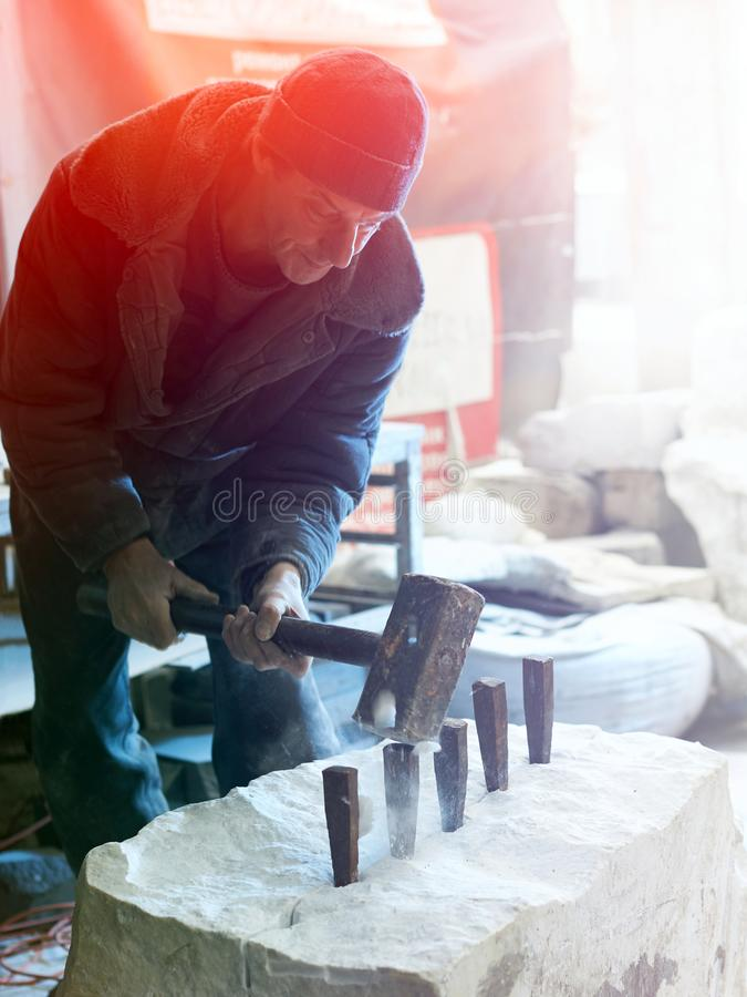 The sculptor of the stone-maker strikes with a heavy hammer on w stock photography