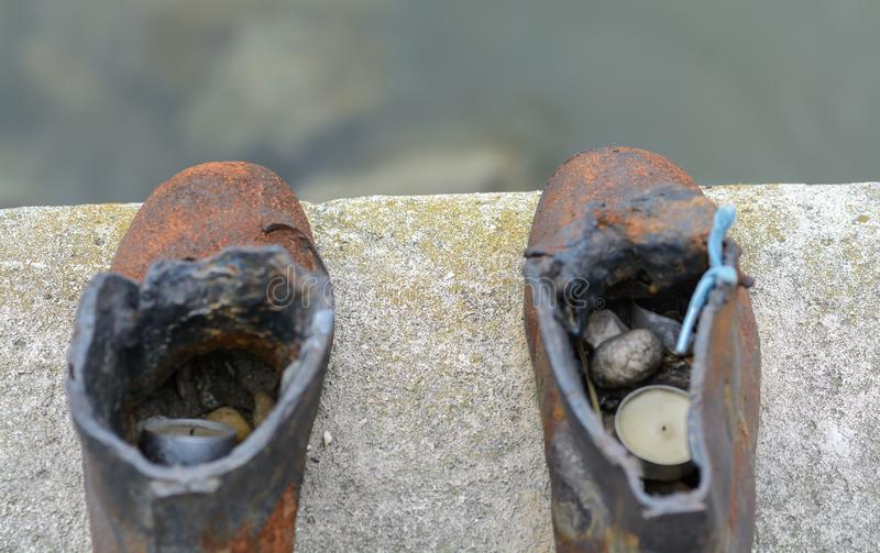 The sculptural composition, cast from cast iron, represents 60 pairs of different men`s, women`s and children`s shoes. Trampled stock photography