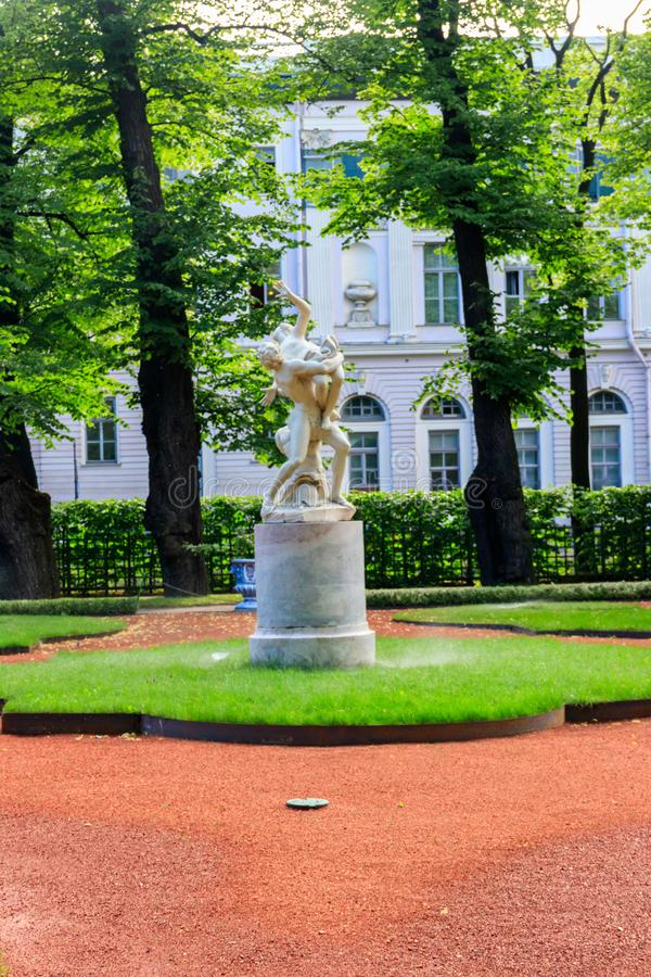 Sculptural composition Kidnapping of Sabine Woman in old city park Summer Garden in St. Petersburg, Russia stock photo