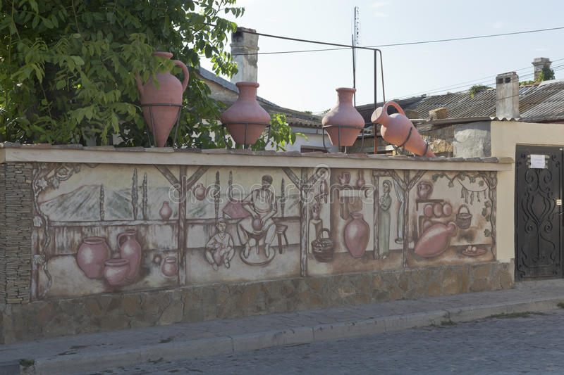 Sculptural composition of pitchers on the wall with a picture of a pottery workshop at the crossroads of Karaimskaya and Krasnoarm stock photo