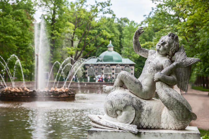 Sculptural group. ST. PETERSBURG, PETERHOF, RUSSIA - JUNE 02, 2016: Sculptural group Cupid on a dolphin fountain Sun in the Lower Gardens of Peterhof. It was stock photography