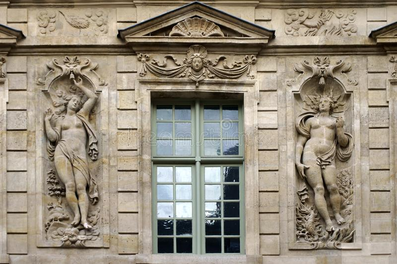 Sculpture reliefs on old house. The sculptural reliefs of two Greek Roman figures on the facade of an old house in Paris royalty free stock image