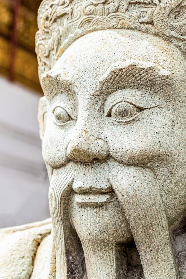 Sculpture of an ancient warrior with large and long whiskers of white stone close up stock image
