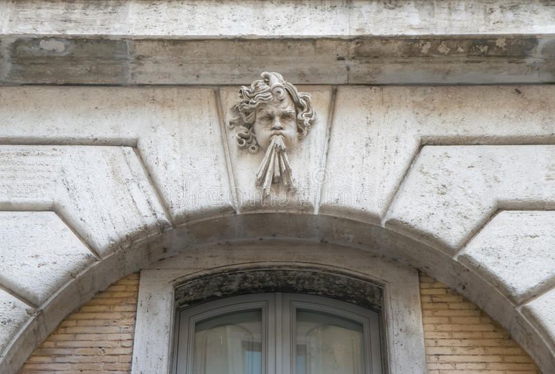 Sculpture of an angel blowing. In the top of an old door in Rome, Italy royalty free stock images