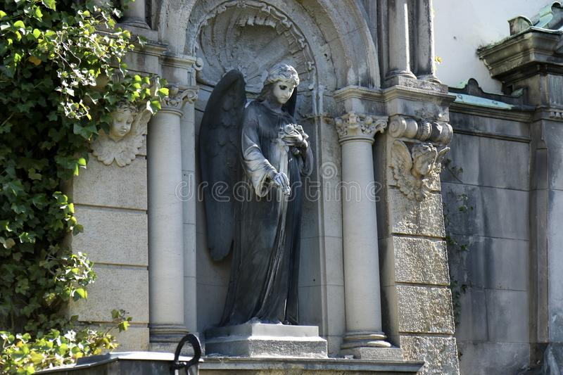 Sculpture of an Angel with flowers roses in her hand on a family tomb / crypt at the cemetery at Suedstern.  stock photos