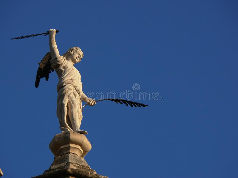 Sculpture of angel with pen and sword royalty free stock photo