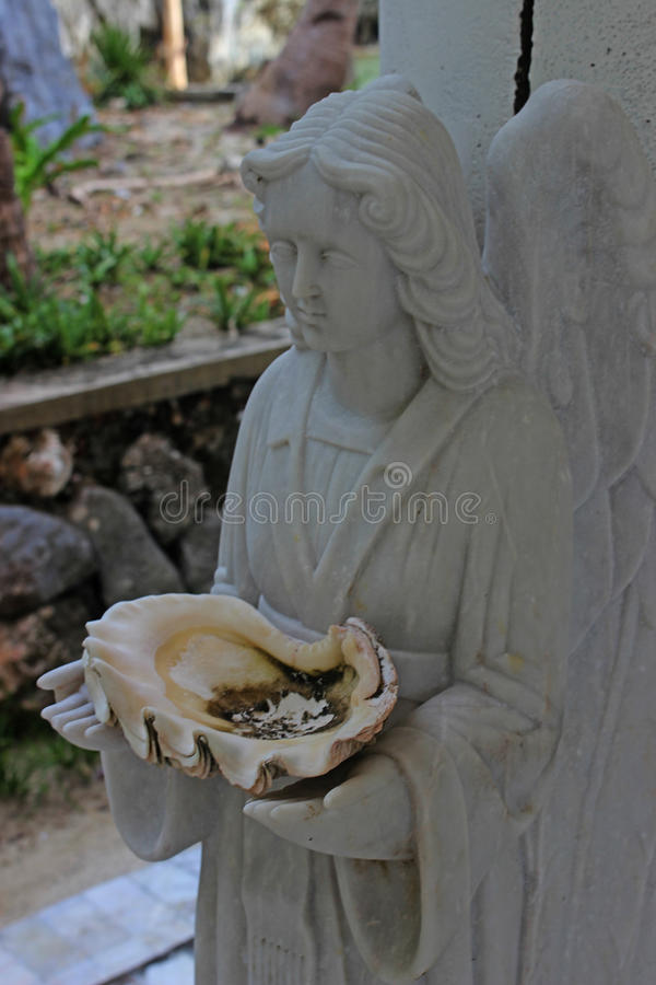 Sculpture of an angel with a sea shell . Philippines. Sculpture of an angel with a sea shell . Palawan Philippines royalty free stock photography