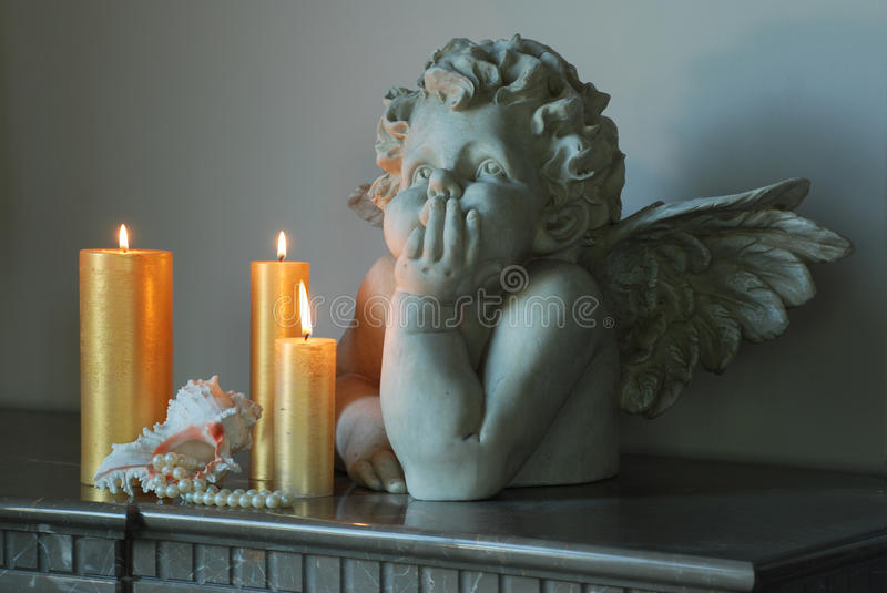 Sculpture of an angel. Standing next candle is shell of her pearl necklace falls stock images