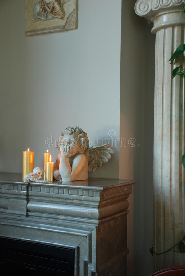 Sculpture of an angel. Standing next candle is shell of her pearl necklace falls stock photography
