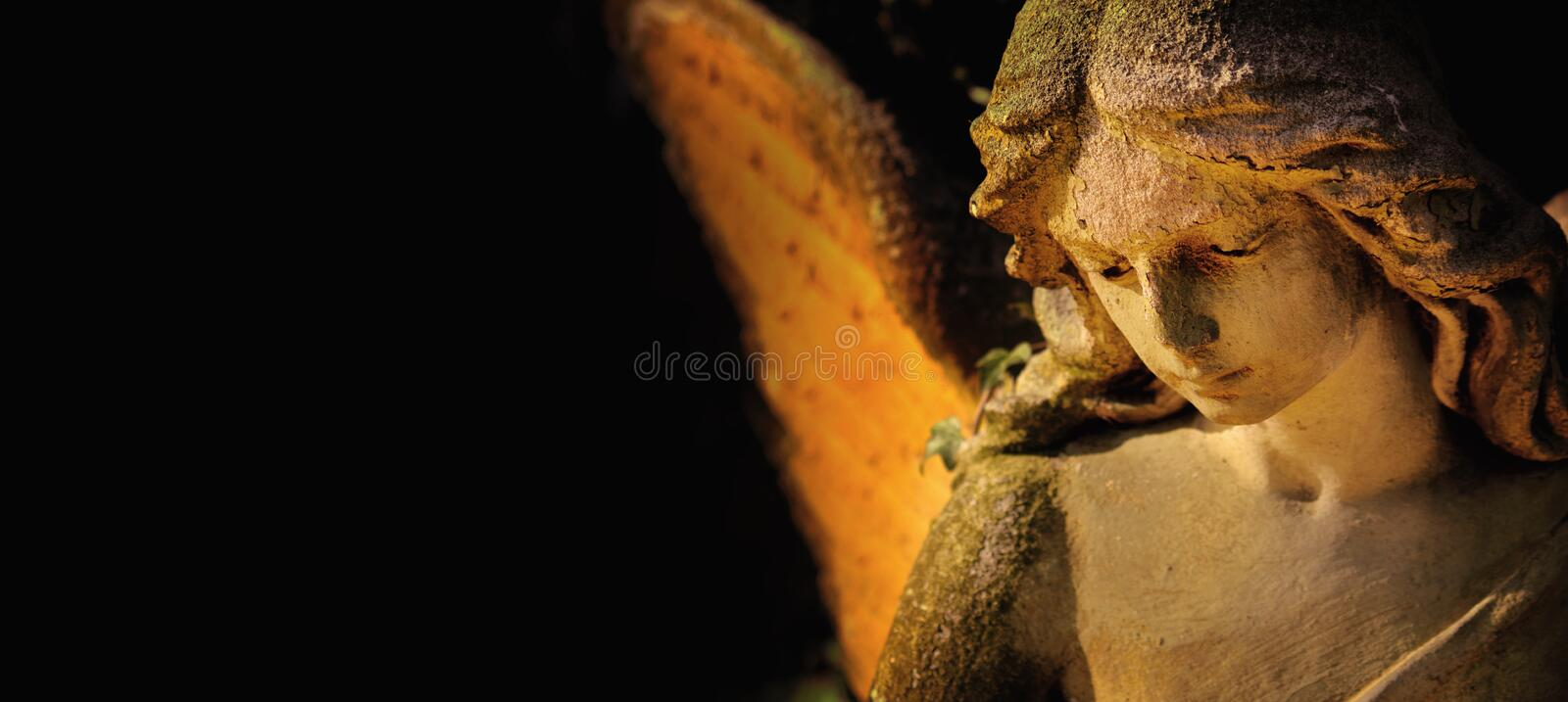 Sculpture of an angel with wings against dark background Religi. Sculpture of gold angel with wings against dark background Religion, faith, Christianity, soul royalty free stock photo