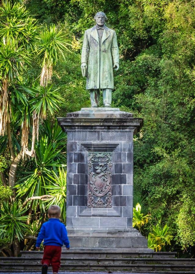 Sculpture in the botanical gardens. Little boy under the sculpture in the José do Canto Botanical Garden in Ponta Delgada, the capital of Sao Miguel island stock photos