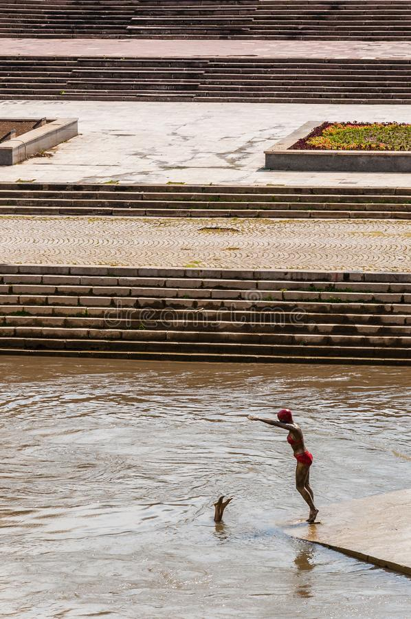 Sculpture of bronze statue of girl swimmer jumping in Vardar river. Waterscape statue Divers on stone coastline stairs background stock image
