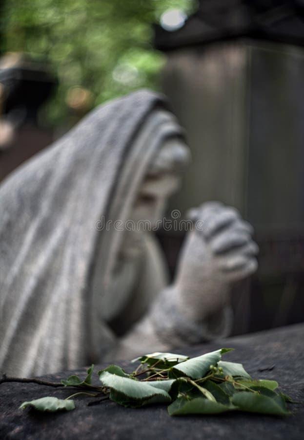 Sculpture brouillée d'une femme s'affligeante au-dessus d'une tombe dedans avec un gre photo libre de droits