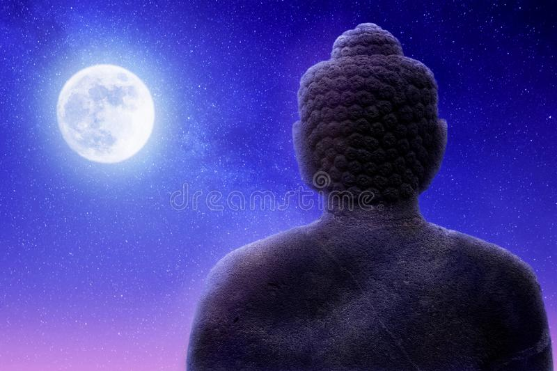 Sculpture of Buddha on a night sky background and moon. Artistic image. royalty free stock image