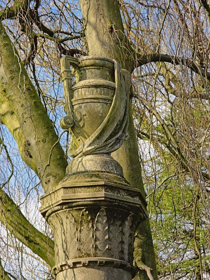 Sculpture décorative en vase sur un pilier avec des lauriers photos stock