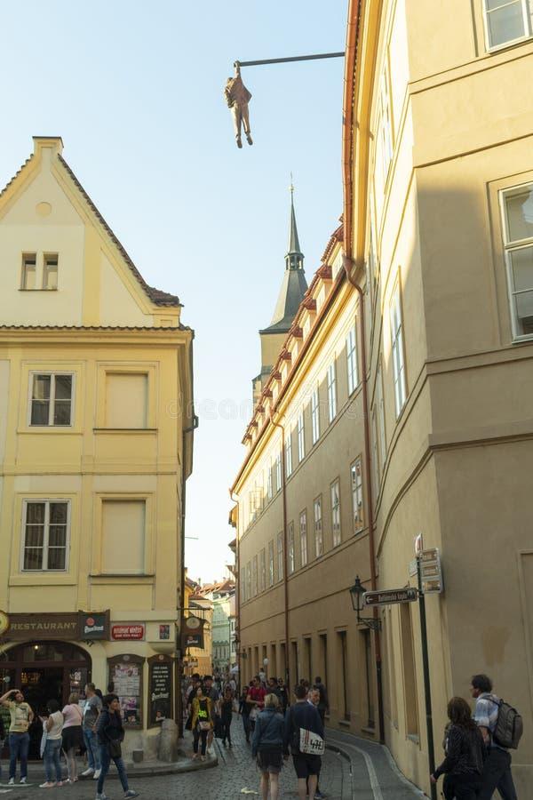 sculpture d'un homme accrochant entre les maisons au centre de la ville images stock