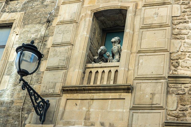 Sculpture d'une fille, d'un garçon et d'un chat regardant par une fenêtre sur la rue Basheni dans la vieille ville de Bakou photographie stock