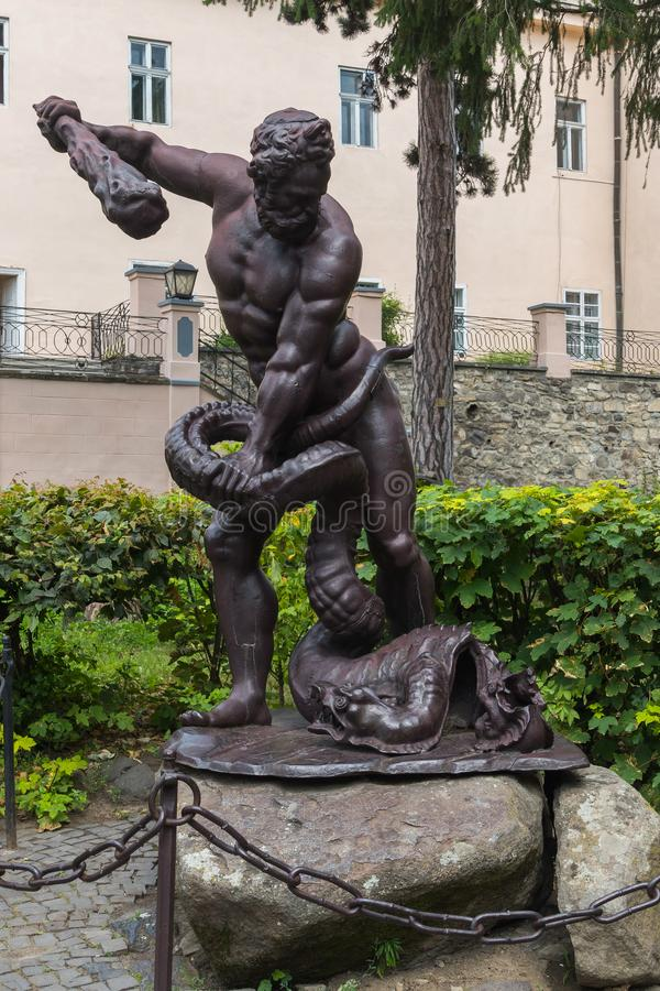 Sculpture depicting a man with a truncheon of a conquering serpent near his feet. Standing on the stones behind the stock photography