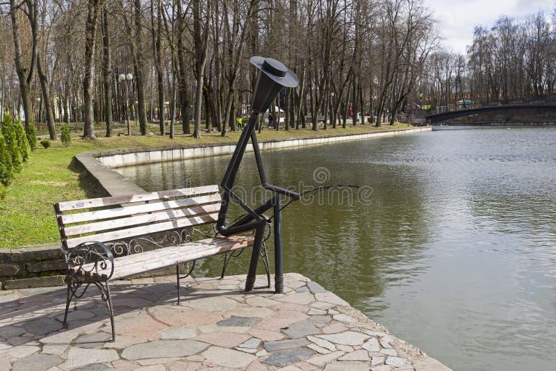 Sculpture drôle en parc - une lanterne sous forme de pêcheur photographie stock libre de droits