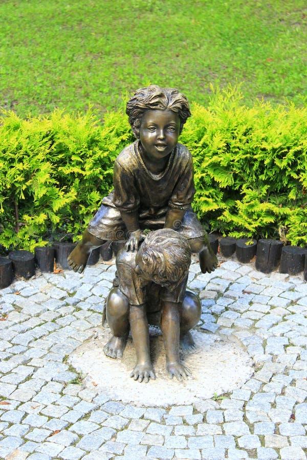 Sculpture en bronze des enfants jouant saute-mouton en parc d'été image libre de droits