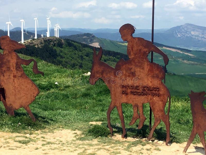 Sculpture en pèlerin d'Alto del Pérdon avec des turbines de vent dans la distance image stock