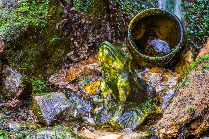 Sculpture en pierre en grenouille avec couler l'eau à l'arrière-plan, architecture d'étang de jardin photographie stock
