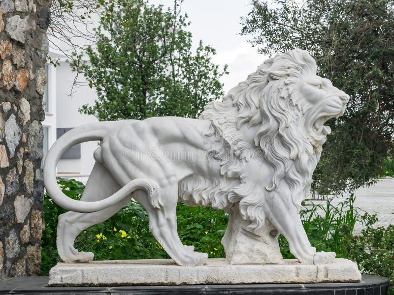 Sculpture en ville d'un lion blanc avec la bouche ouverte à l'entrée Point de repère local photos stock
