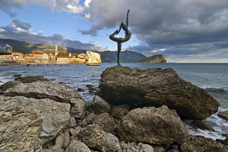 Sculpture girl dancing. Against the backdrop of the old town of Budva royalty free stock images
