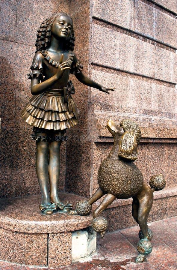 Sculpture of a girl with a dog stock photos