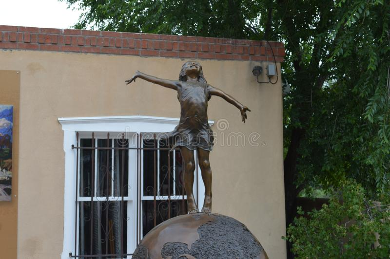 Sculpture of Girl on Globe in Sante Fe New Mexico. Celebratory Girl on Earth Globe in Front of Artist Gallery in Santa Fe New Mexico royalty free stock images
