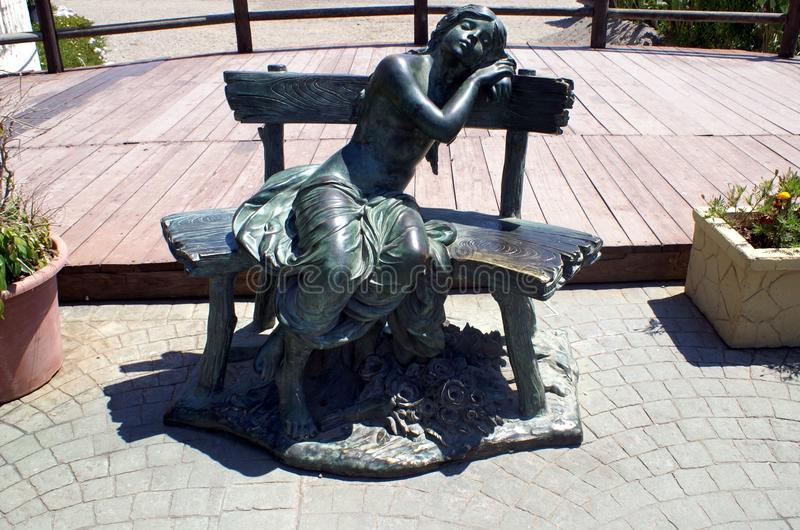 Sculpture of a girl relaxing on a seat at Marbella beach, Andalusia, Spain, Europe. Outdoor decoration of a bronze sculpture of a girl relaxing on a bench at royalty free stock photography