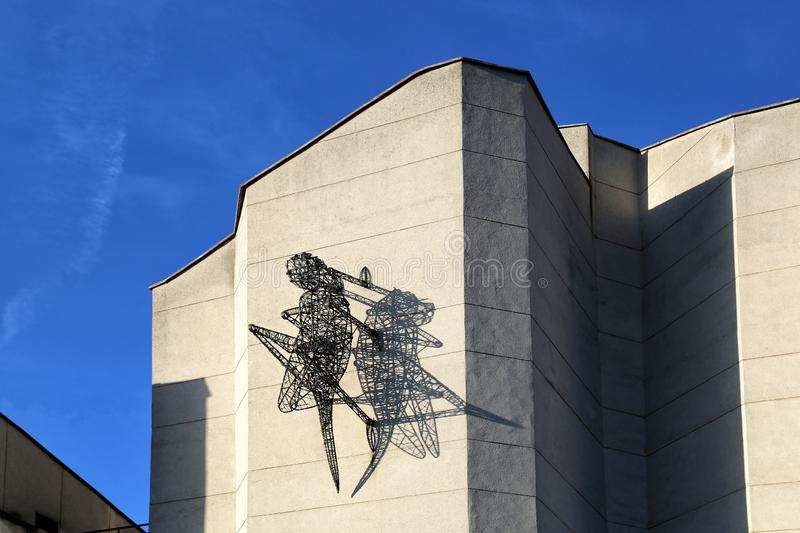 Sculpture of a grasshopper made of steel and copper wire on the wall of a building royalty free stock photo