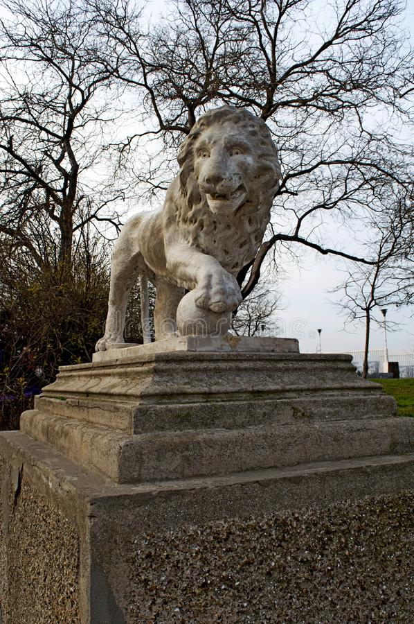 Sculpture of a lion on a pedestal in a park royalty free stock photo