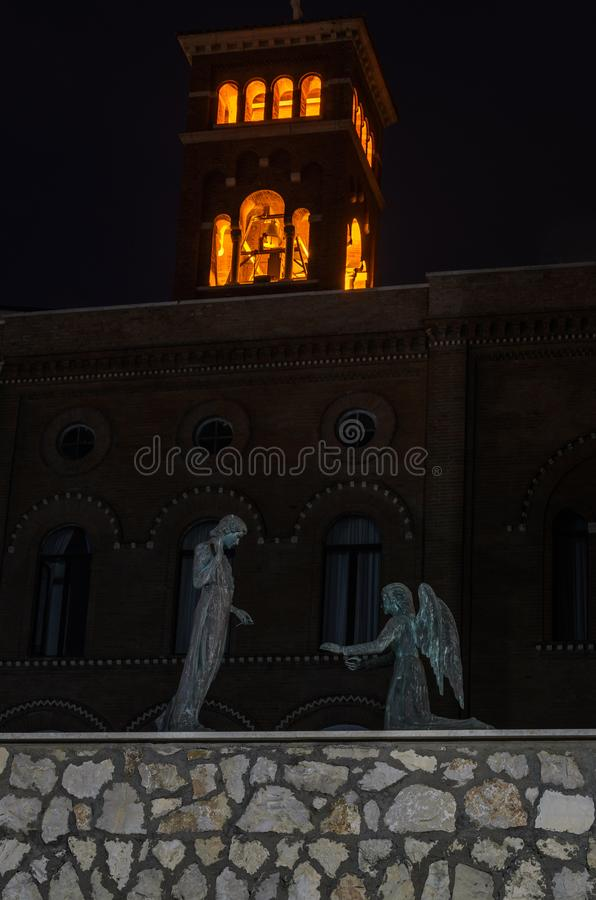 Sculpture with a man and angels on their knees on the embankment at night Nettuno, Italy.  stock photo